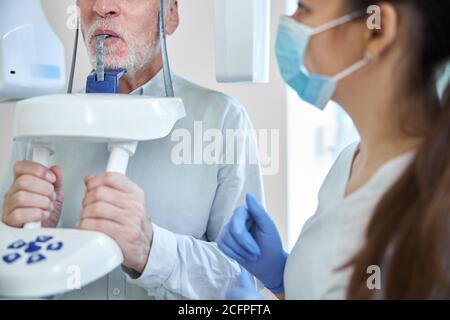 Femme experte dentaire préparant un homme âgé pour la radiographie dentaire Banque D'Images