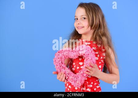 Bonne fille tenant coeur rose sur fond bleu. Enfant adorable avec de longs cheveux souriant dans une robe rouge. Fête de la Saint-Valentin. Gentillesse et tendresse. Concept romantique d'amour, espace copie Banque D'Images