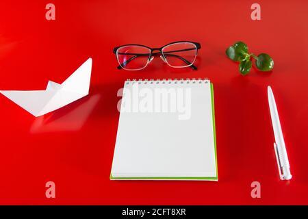 Fournitures de bureau sur fond rouge. Bloc-notes, stylo et lunettes vierges. Mise en page pour le design dans le style du minimalisme.