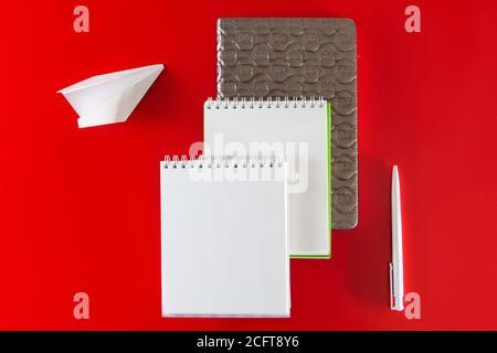 Design minimaliste. Fournitures de bureau - carnets et stylos sur fond rouge.