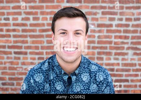 Un portrait d'un homme dans un bouton bleu vers le bas chemise contre un mur de briques