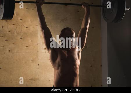 Mettre en place des barres de levage de jeune homme à l'accent, l'entraînement en salle de sport Banque D'Images