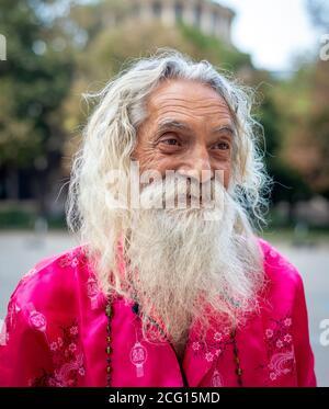 Homme senior portrait d'homme flamboyant barbu avec long Cheveux blancs portant des vêtements roses dans les rues de Sofia Bulgarie Banque D'Images