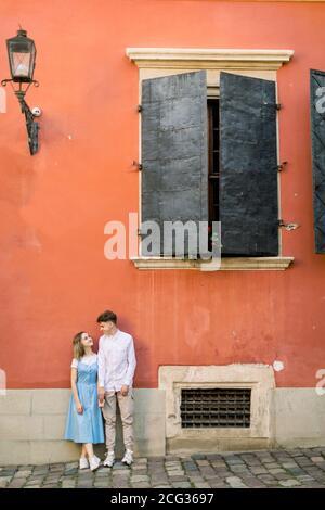 Portrait d'un couple amoureux près du vieux bâtiment orange vintage. Homme heureux et fille en robe bleue, debout sur le mur de l'ancien bâtiment et