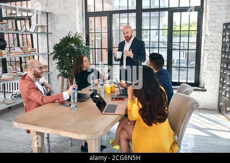 Tiré d'un groupe de jeunes professionnels ayant une réunion d'affaires. Groupe diversifié de jeunes designers smiling lors d'une rencontre à l'office.