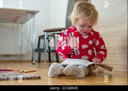 Jolie fille assise sur le sol et dessin dans un carnet.