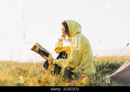 Jeune femme voyageur à capuchon jaune lisant le livre contre la tente. Tourisme local, week-end