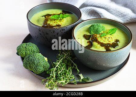 Soupe verte de brocoli ou d'épinards avec huile épicée aromatique dans un bol. Nourriture saine végétalienne. Arrière-plan en pierre.