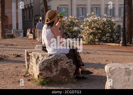 Rome, Italie - 27 juin 2010 : une touriste, portant un chapeau, repose sur un bloc de pierre, buvant une bière, dans la région du Forum romain, Rome.