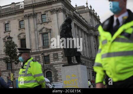 Les policiers se tiennent comme un graffiti est vu sur la statue de Winston Churchill, à Londres, en Grande-Bretagne le 10 septembre 2020. REUTERS/Simon Dawson Banque D'Images