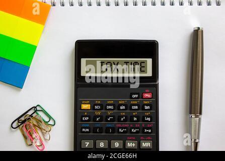 Calculatrice avec inscription « TAX Time », note blanche, papier de couleur, trombones, stylo. Concept d'entreprise.