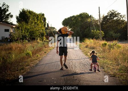 Petite fille, à vélo, avec son jeune père portant une grosse citrouille d'halloween sur une route de campagne au coucher du soleil. Vue arrière.
