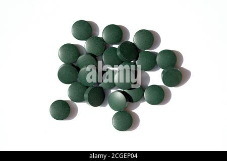 Arrondir les pilules vertes sur un fond blanc vue du dessus. Les comprimés de Chlorella sont des suppléments alimentaires. Spiruline sous forme de pilule.