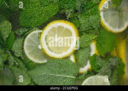 Fond de citron et de menthe dans un récipient en verre froid. Citrons frais et limonade à la menthe dans une bouteille en gros plan. Verre recouvert de gouttelettes d'eau. Naturel