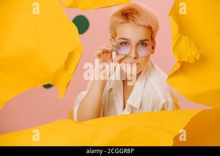 Femme stricte regardant à travers un trou large dans un grand feuille de papier jaune étroit Banque D'Images