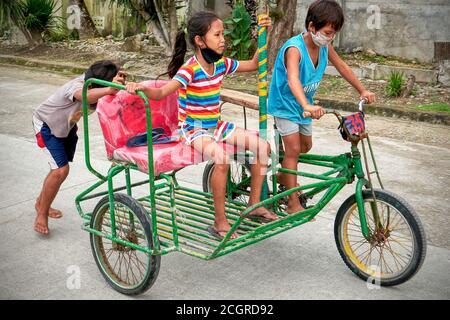 Trois jeunes enfants barefootés portant un masque de visage sur un pédicab peint traditionnel coloré sur une route sur l'île de Boracay, Philippines, Asie