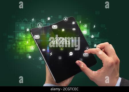 Businessman holding a smartphone pliable avec inscription de la statistique sociale, réseaux sociaux concept