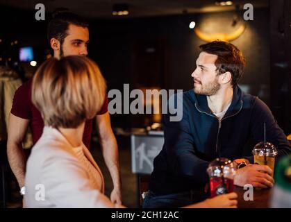 Portrait de jeunes étudiants gaies amis hommes et femme buvant des cocktails tout en parlant dans un café. Groupe de jeunes se réunir dans un café. Banque D'Images