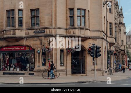 Oxford, Royaume-Uni - 04 août 2020 : un couple portant des masques sur une rue haute d'Oxford, une ville d'Angleterre célèbre pour sa prestigieuse université, établit