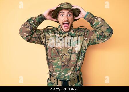Jeune homme caucasien portant l'uniforme militaire de camouflage fou et effrayé avec les mains sur la tête, peur et surpris de choc avec la bouche ouverte Banque D'Images