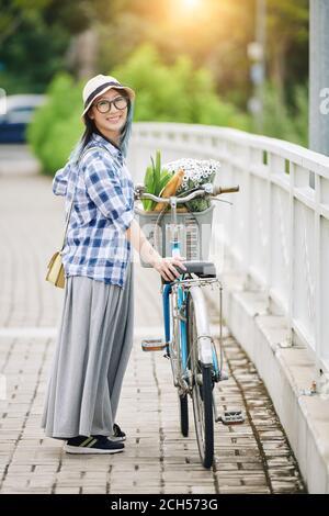 Femme chinoise debout à côté de son vélo Banque D'Images