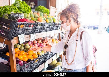 Femme caucasienne porter un masque de protection pour covid-19 coronavirus et acheter quelques fruits et légumes dans le magasin local pour un mode de vie sain et la sécurité