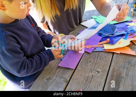 Un jeune enfant de 3 ans apprend à couper du papier avec des ciseaux assis à l'extérieur sur une table avec papier d'art coloré Carmarthenshire pays de Galles Royaume-Uni KATHY DEWITT