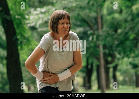 Jogging féminin avec grimace douloureux de visage après avoir ressenti la douleur dans abaisser l'abdomen pendant la course en position de stationnement Banque D'Images