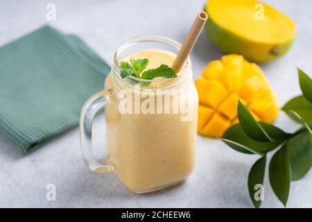 Délicieux smoothie végétarien à la mangue dans un verre avec boisson au bambou paille