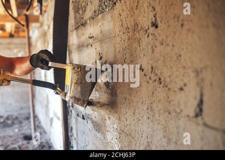 Homme plâtrage un mur avec du mortier à l'aide d'un seau de trémie
