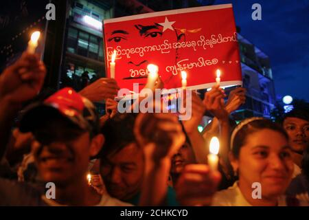 Supporters of Myanmar's opposition leader Aung San Suu Kyi hold candles and a banner in her support during a protest against the shortage of electricity after she addressed them in Yangon May 25, 2012. A week of protests in Myanmar over chronic power outages gained momentum on Friday after opposition leader Aung San Suu Kyi gave them her blessing and the government's response added to popular outrage.   REUTERS/Damir Sagolj (MYANMAR - Tags: POLITICS CIVIL UNREST ENERGY)