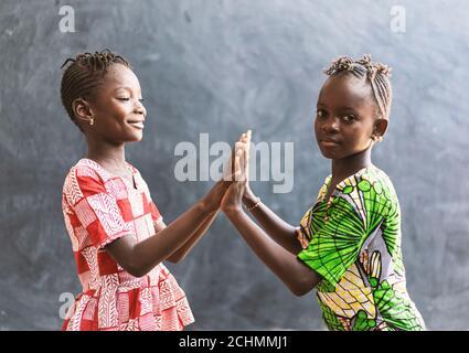 Les enfants noirs africains jouant avec les mains souriantes