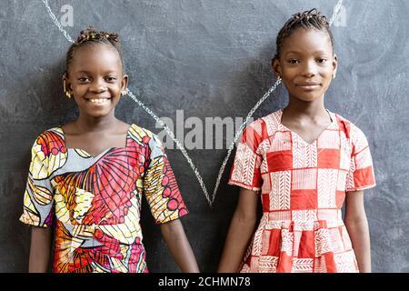 De magnifiques sœurs africaines posant, souriant et riant heureux devant le Blackboard à l'école