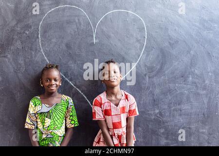 Deux jolies petites filles noires africaines debout devant Tableau noir avec symbole « Big Heart Love »