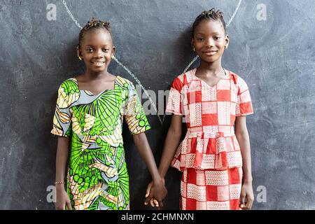 Couple d'enfants africains posant à l'intérieur dans la tenue d'un bâtiment scolaire Mains