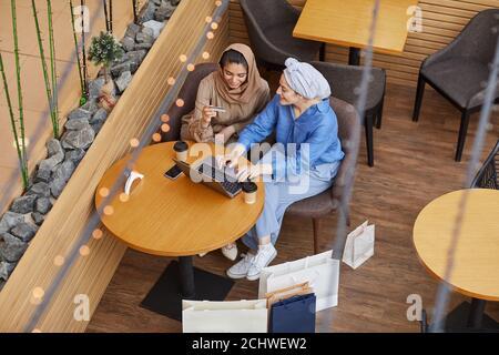 Vue panoramique de deux jeunes femmes du Moyen-Orient qui profitent de leurs achats en ligne via un ordinateur portable tout en étant assis dans un café du centre commercial et en tenant une carte de crédit, un espace de copie