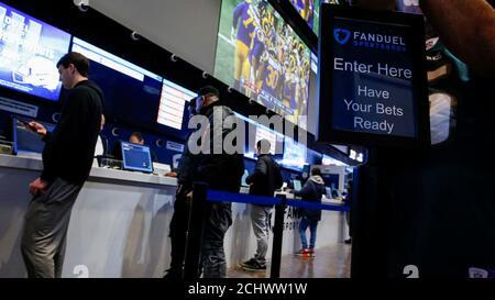 Les gens font leurs Paris au sportsbook de FANDUEL pendant le Super Bowl LIII à East Rutherford, New Jersey, États-Unis, le 3 février 2019. REUTERS/Eduardo Munoz