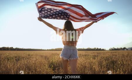Jeune fille américaine heureuse courant et sautant le 4 juillet sans souci avec les bras ouverts sur le champ de blé. Drapeau des États-Unis. Banque D'Images