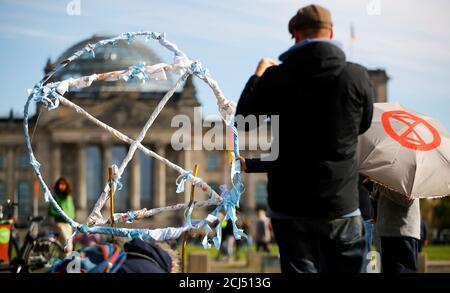 Les gens ont mis en place un symbole de rébellion d'extinction (XR) dans un camp de fortune de militants du climat à côté du bâtiment du Reichstag à Berlin, en Allemagne, le 6 octobre 2019. REUTERS/Hannibal Hanschke