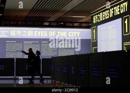 """Les gens marchent devant l'exposition """"les yeux de la ville"""" dans le cadre d'une Biennale commune Hong Kong/Shenzhen d'Urbanisme et d'architecture à la gare de Futian à Shenzhen, Chine 23 décembre 2019. Photo prise le 23 décembre 2019. REUTERS/Jason Lee"""