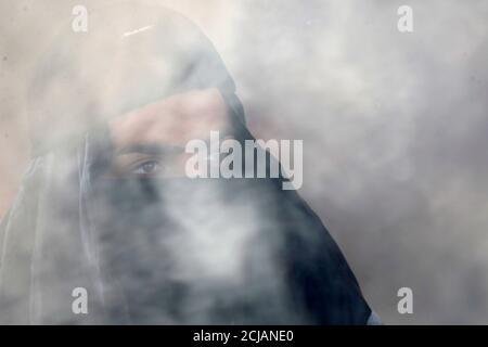 Un démonstrateur irakien se cache le visage au milieu de la fumée des pneus en feu lors des manifestations anti-gouvernementales en cours à Najaf, Irak, le 21 janvier 2020. REUTERS/Alaa al-Marjani