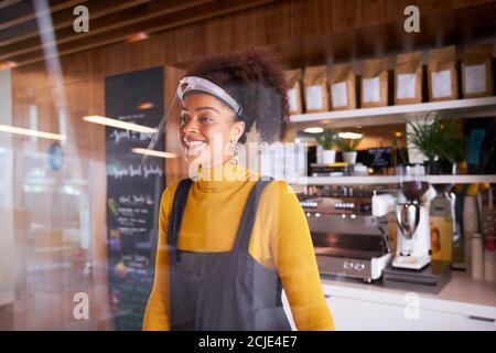 Femme propriétaire d'une petite entreprise du café-restaurant portant un masque facial En coulisses pendant une pandémie de santé Banque D'Images