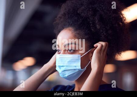 Femme Docteur en gommages mettant sur le masque de visage sous pression Dans l'hôpital occupé pendant la pandémie de santé Banque D'Images