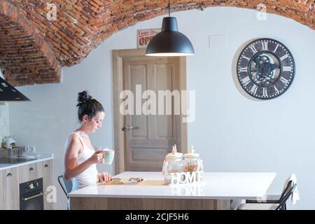 jeune fille brune lisant un magazine tout en buvant du café la cuisine