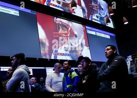 Les gens regardent le jeu après avoir fait leurs Paris au sportsbook FANDUEL pendant le Super Bowl LIII à East Rutherford, New Jersey, États-Unis, le 3 février 2019. REUTERS/Eduardo Munoz