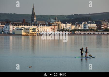 Deux paddle-boarders à Weymouth Bay à Dawn, Jurassic Coast, Dorset, Angleterre, Royaume-Uni