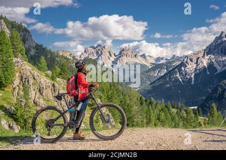 Belle et active femme senior à cheval son vélo électrique de montagne sur le haut plateau de Prato Piazzzo dans les trois pics Dolomites, silhouette rocheuse de