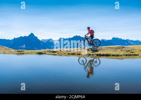 Belle femme à cheval sur son vélo électrique de montagne les trois pics Dolomites, se reflétant dans l'eau bleue d'un lac de montagne froid