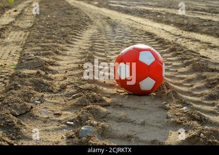Utilisé ballon de soccer rouge et blanc sur terre sale Banque D'Images