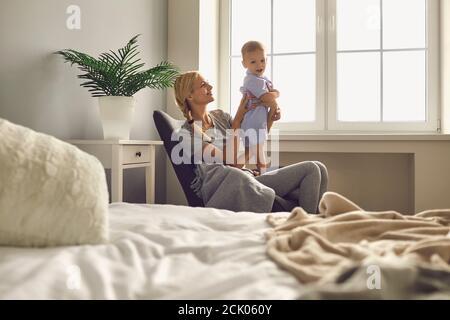 Maman avec un petit fils assis dans une chaise près d'une grande fenêtre dans une chambre lumineuse. Banque D'Images